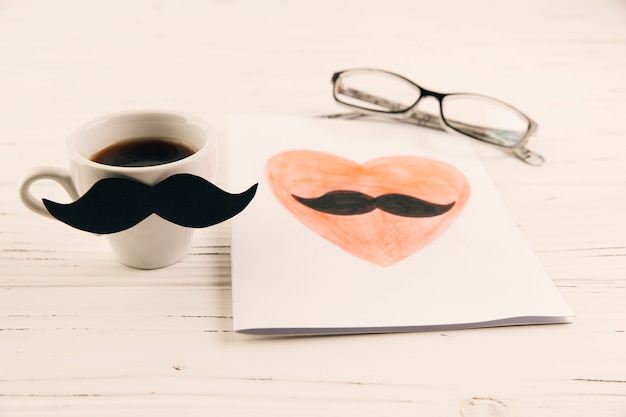 Zeichnen auf papier nahe cup des getränks und der brillen