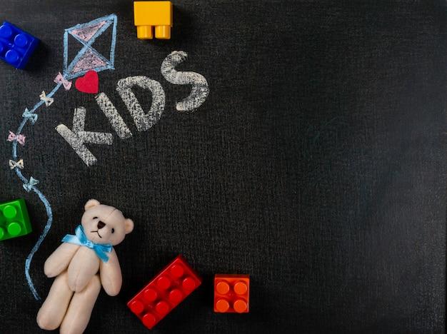 Zeichnen auf sandpapier. die kinder, die auf tafel und teddybären mit geschrieben werden, bauen stücke zusammen. hintergrund textfreiraum.