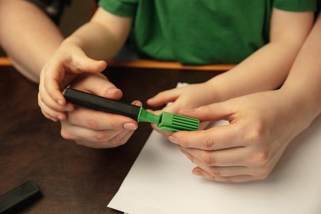 Zeichnen mit bunten markern. nahaufnahme von frauen- und kinderhänden, die verschiedene dinge zusammen tun. familie, zuhause, bildung, kindheit, wohltätigkeitskonzept. mutter und sohn oder tochter, studieren.