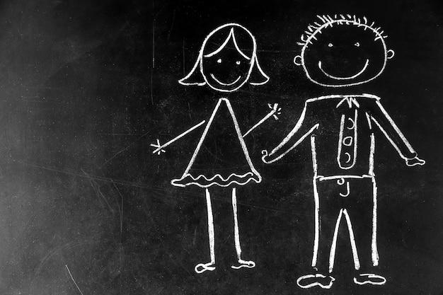 Zeichnen mit kreide auf schwarzem hintergrund junge und mädchen, das konzept der freundschaft