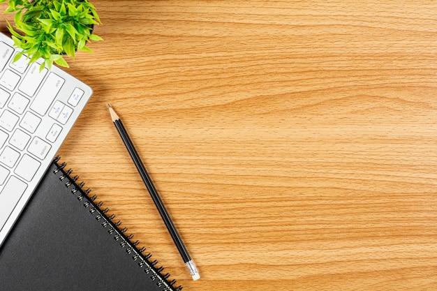 Zeichnen sie mit einer computertastatur und einem notizbuch auf hölzernem schreibtisch an