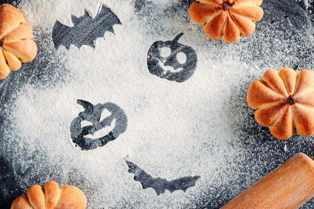 Zeichnende halloween-dekorationen auf mehlhintergrund, kuchen in form des kürbises und des nudelholzes. halloween-kochkonzept