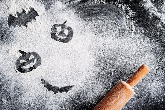 Zeichnender halloween-kürbis und -schläger auf dem mehlhintergrund und -nudelholz. halloween-kochkonzept
