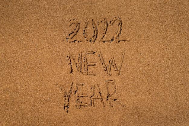 Zeichnet auf sand an einem strand mit einer welle am meer urlaub am meer neujahrskonzept