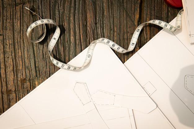 Zeichnungen und maßband werden auf den holztisch gelegt