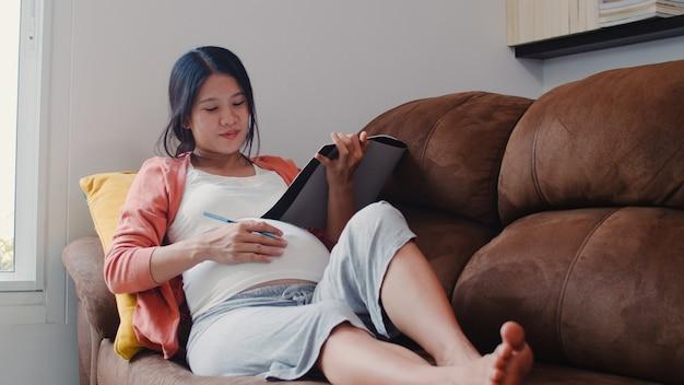 Zeichnungsbaby der schwangeren frau des jungen asiaten im bauch im notizbuch. die mutter, die glücklich sich fühlt, positiv und ruhig lächelnd, während mach s gut das kind, das zu hause auf sofa im wohnzimmer liegt.