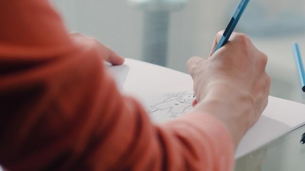 Zeichnungsbaby der schwangeren frau des jungen asiaten im bauch und in der familie im notizbuch. die mutter, die sich glücklich fühlt, positiv und ruhig lächelnd, während sich kind auf tabelle im wohnzimmer zu hause kümmern.