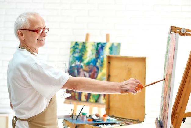 Zeichnungsbild des begabten männlichen malers im kunststudio unter verwendung der farbe und des pinsels.
