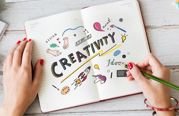 Zeichnungskreativität der jungen frau in einem notizbuch