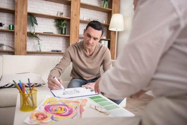 Zeichnungsserie. konzentrierter kräftiger mann, der psychologen beim zeichnen des bildes besucht