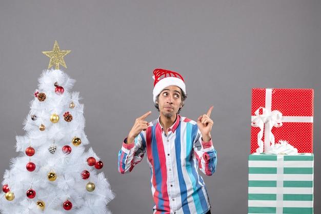 Zeigefinger des jungen mannes der vorderansicht, der etwas zeigt, das nahe weißem weihnachtsbaum steht