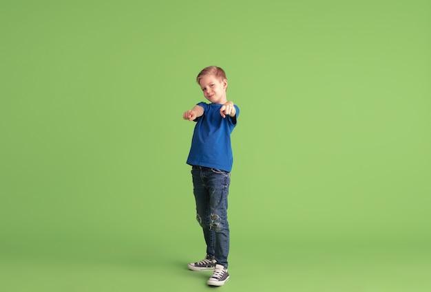 Zeigen auf. fröhlicher junge, der auf grüner wand spielt und spaß hat. kaukasisches kind in hellem tuch sieht verspielt aus, lacht und lächelt. konzept der bildung, kindheit, emotionen, gesichtsausdruck.