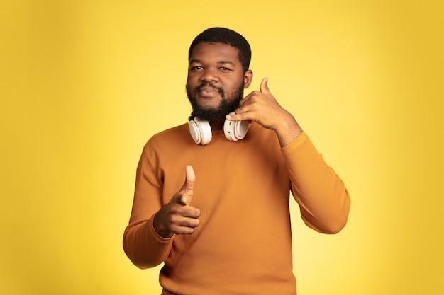 Zeigen, das das porträt des jungen afroamerikaners lokalisiert auf gelb wählt
