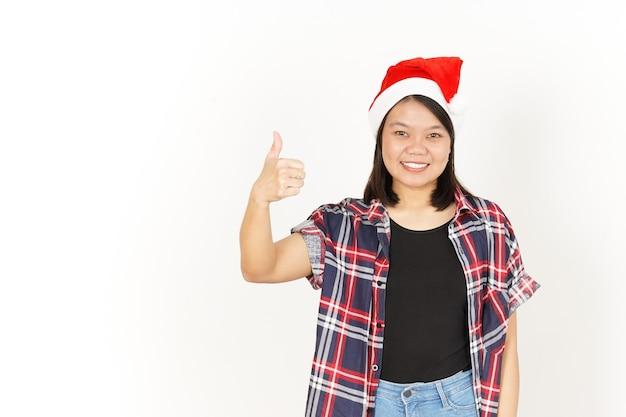 Zeigen daumen hoch der schönen asiatischen frau mit rotem kariertem hemd und weihnachtsmütze isoliert auf weiß