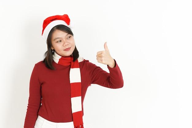 Zeigen daumen hoch zeichen der asiatischen frau mit rotem rollkragenpullover und weihnachtsmütze isoliert auf weiß