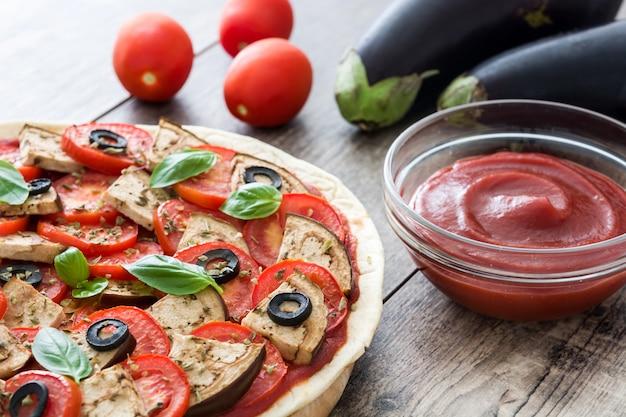 Zeigen der vegetarischen pizza mit aubergine, tomate, schwarzen oliven, oregano und basilikum auf holztisch