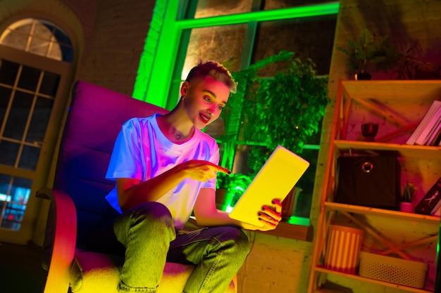 Zeigen. filmporträt der stilvollen frau im neonbeleuchteten innenraum. getönt wie kinoeffekte, leuchtende neonfarben. kaukasisches modell mit tablette in bunten lichtern drinnen. jugendkultur.