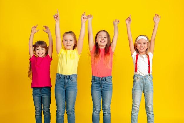 Zeigen. glückliche kinder, die zusammen an der gelben studiowand spielen und spaß haben.