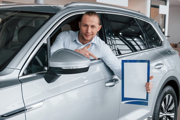 Zeigen mit dem zeigefinger. manager, der im modernen weißen auto mit papier und dokumenten in den händen sitzt