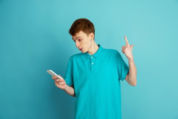 Zeigen mit telefon. das moderne porträt des kaukasischen jungen mannes lokalisiert auf blauer wand, monochrom. schönes männliches model. konzept der menschlichen emotionen, gesichtsausdruck, verkauf, anzeige, trendy.