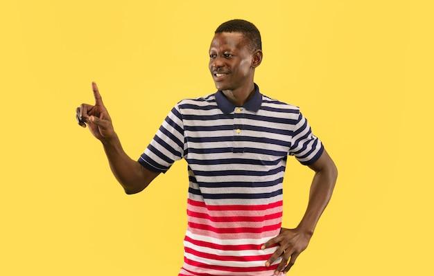 Zeigen sie auf sie. junger afroamerikanermann lokalisiert auf gelbem studiohintergrund, gesichtsausdruck. schönes männliches porträt der halben länge. konzept menschlicher emotionen, gesichtsausdruck.