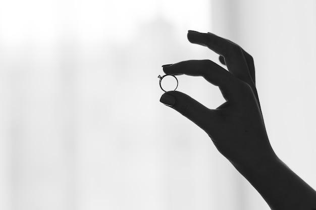 Zeigen sie ring auf dem finger, der auf weißem hintergrund lokalisiert wird