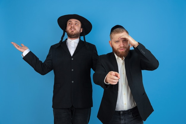 Zeigen, wählen. porträt eines jungen orthodoxen jüdischen mannes lokalisiert auf blauer wand. purim, geschäft, festival, urlaub, feier pessach oder pessach, judentum, religionskonzept.