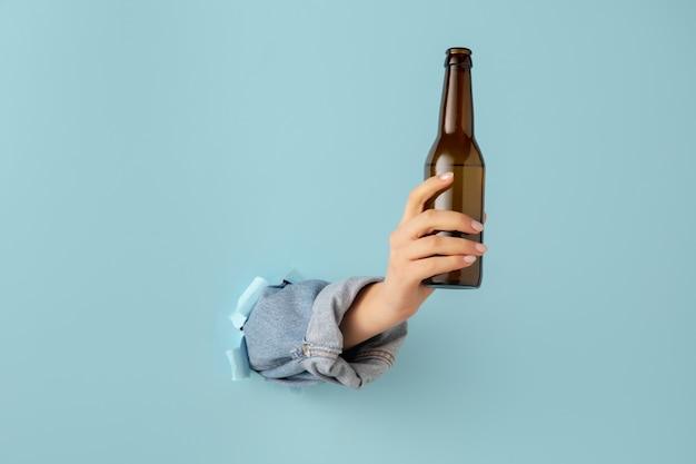 Zeigen. weibliche hand gestikuliert in zerrissenem blauem papierlochhintergrund. aufbrechen, durchbrechen. konzept von geschäft, finanzen, einkaufen, angebot, verkauf, anzeige.