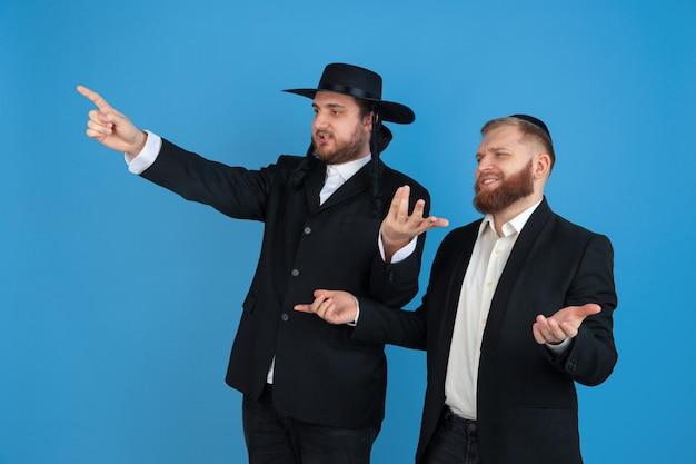 Zeigend, einladend. porträt eines jungen orthodoxen jüdischen mannes lokalisiert auf blauer wand. purim, geschäft, festival, urlaub, feier pessach oder pessach, judentum, religionskonzept.