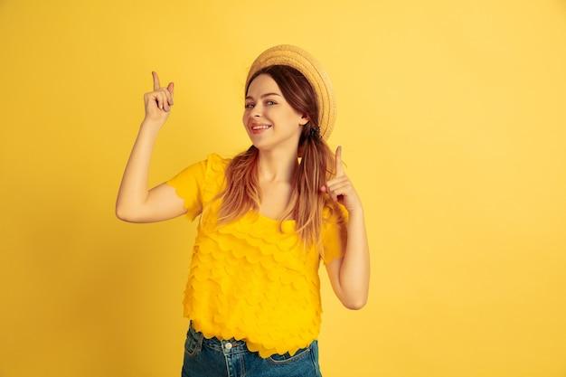 Zeigend, lächelnd. porträt der kaukasischen frau auf gelbem studiohintergrund. schönes weibliches modell im hut. konzept der menschlichen emotionen, gesichtsausdruck, verkauf, anzeige. sommerzeit, reisen, resort.