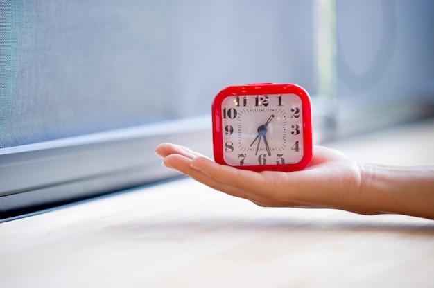 Zeiger und roter wecker, der den alarm überhaupt anzeigt. jeden morgen