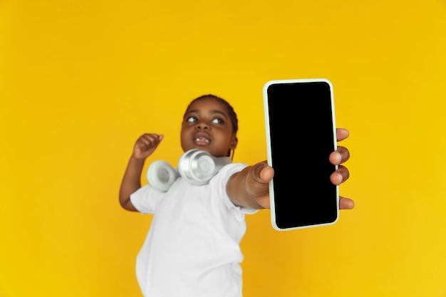 Zeigt den bildschirm des leeren telefons an und zeigt. porträt des kleinen afroamerikanischen mädchens auf gelbem studiohintergrund. fröhliches kind. konzept der menschlichen emotionen, ausdruck, verkauf, anzeige. exemplar. sieht süß aus.