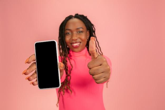 Zeigt den telefonbildschirm an. glückliche junge schöne afroamerikanerfrau lokalisiert auf rosa hintergrund. kopieren sie platz für anzeige, design. aufnahme in halber länge. konzept der menschlichen emotionen, gesichtsausdruck.