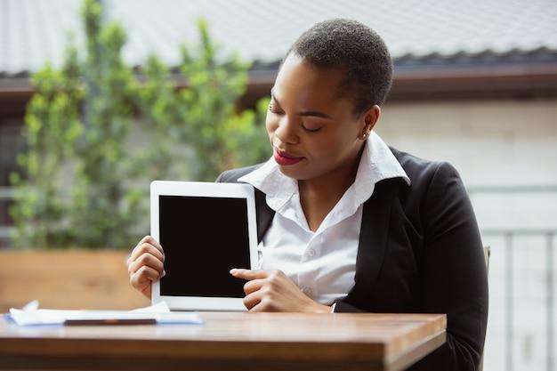 Zeigt einen leeren tablet-bildschirm an. afroamerikanische geschäftsfrau in bürokleidung lächelnd, sieht selbstbewusst und beschäftigt aus. finanzen, wirtschaft, gleichstellung, menschenrechtskonzept. schönes junges weibliches modell, erfolgreich.