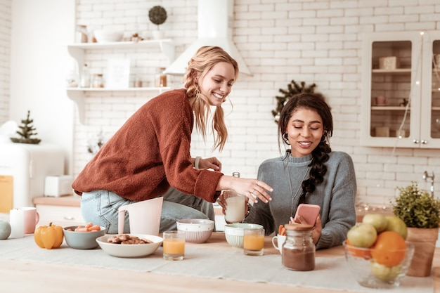 Zeigt lustiges bild. zufriedene attraktive freundinnen, die informationen auf dem smartphone beobachten, während sie morgens zeit in der küche verbringen