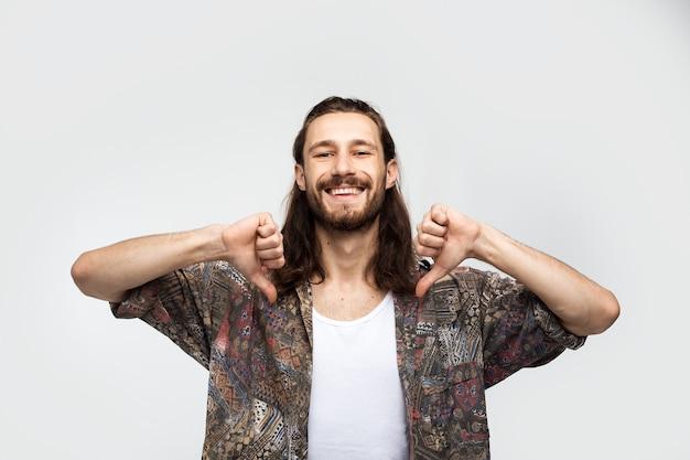 Zeigt sich, ein selbstbewusster mann zeigt mit zwei fingern auf sich. stilvoller sorgloser mann des hipster-reisenden auf einem weißen studiohintergrund, menschenlebensstil