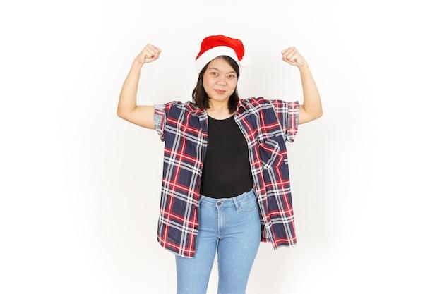 Zeigt stärke und aufstiegsarme der schönen asiatischen frau, die rotes kariertes hemd und weihnachtsmütze trägt