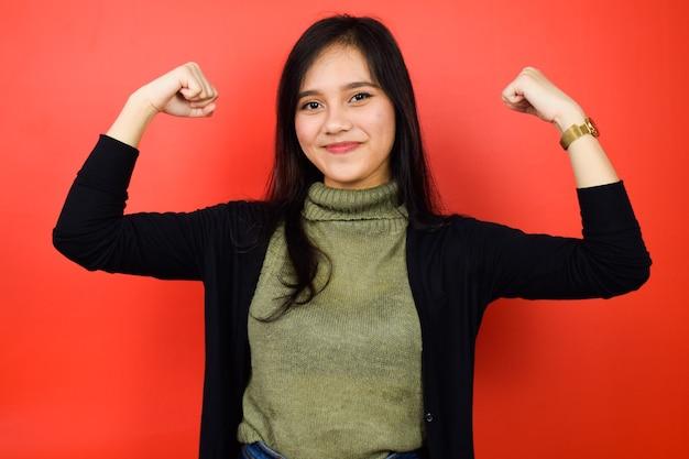 Zeigt stärke und lächeln junger schöner asiatischer frauen mit schwarzem pullover isoliert auf rot