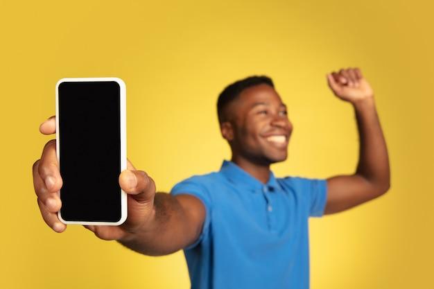 Zeigt telefonbildschirm, gewinner. porträt des jungen afroamerikaners lokalisiert auf gelbem studiohintergrund, gesichtsausdruck. schönes männliches model, exemplar. konzept der menschlichen emotionen, verkäufe, anzeige.