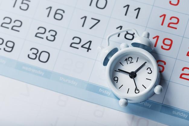Zeit auf einem weißen wecker, der auf dem kalender und einem blauen hintergrund liegt. ansicht von oben