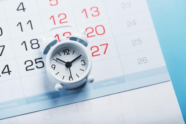Zeit auf einem weißen wecker, der auf dem kalender und einem blauen hintergrund liegt.