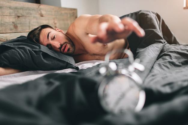 Zeit aufzuwachen. müder mann im bett nicht glücklich. reifer kerl, der wecker bei der prüfung der zeit auf arbeit hält