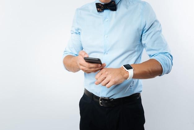 Zeit einstellungen. netter angenehm gut aussehender mann, der auf seine uhr schaut und sein smartphone hält, während er es aufstellt