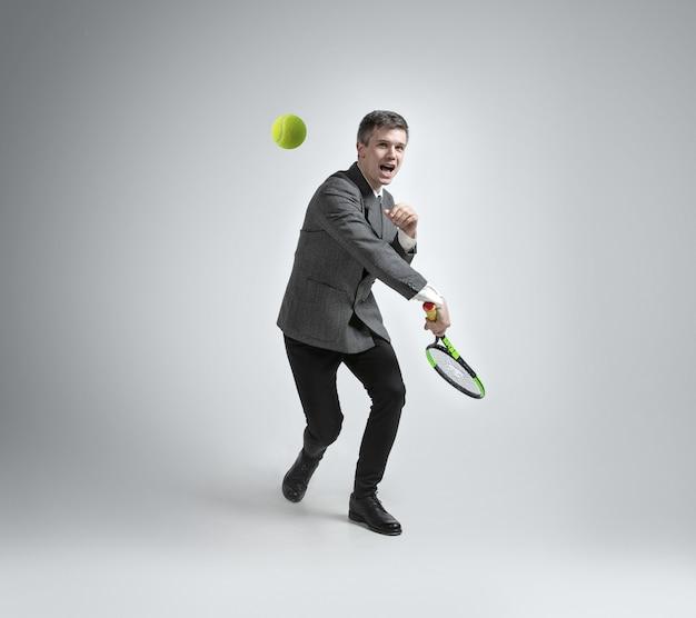 Zeit für bewegung. mann in bürokleidung spielt tennis isoliert auf grauem hintergrund