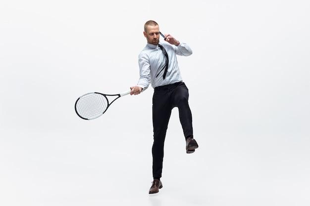 Zeit für bewegung. mann in bürokleidung spielt tennis isoliert auf weiß. geschäftsmann training in bewegung, aktion. ungewöhnlicher look für sportler, neue aktivität. sport, gesunder lebensstil.