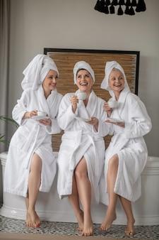 Zeit für dich. drei fröhliche kommunizierende, entspannte barfußfrauen in weißen bademänteln mit tassen im spa-salon