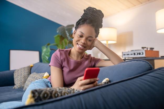 Zeit für dich. junge erwachsene schöne afroamerikanische frau im t-shirt, die lächelnd auf das smartphone schaut, das auf dem sofa sitzt