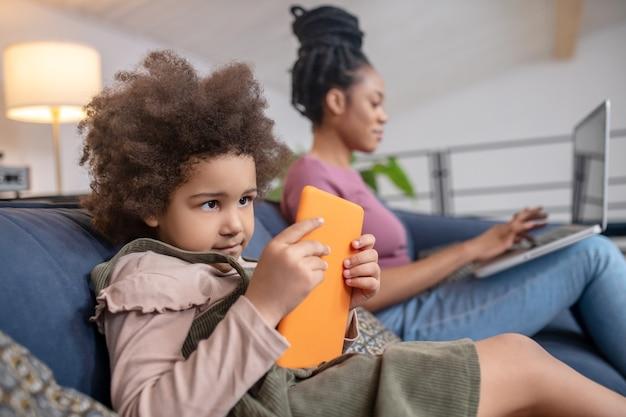 Zeit für dich. wenig beteiligtes afroamerikanisches mädchen, das tablet und frau betrachtet, die am laptop hinten auf dem sofa arbeitet