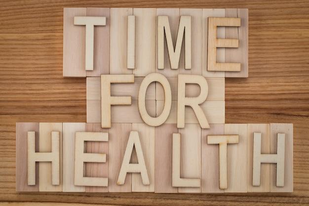 Zeit für die gesundheit - text in vintage-buchstaben auf holzklötzen. medizin-konzept.