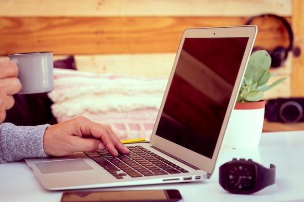 Zeit für eine kaffeepause. freiberufler auf einem weißen tisch mit holzhintergrund. eine ältere frau, die am laptop im freien arbeitet. geräte und kamera in ihrer nähe